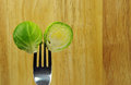Brussel sprout and fork cut silver on wooden background Stock Photo