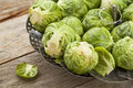 Brussels sprouts in a metal steamer basket on wooden table Stock Photo