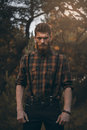 Brutal bearded man in forest outdoor standing alone with sunset nature on background Royalty Free Stock Images