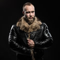 Brutal handsome glum unshaven man with long beard and moustache in black fur coat collar Stock Image