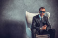 Brutal sexy businessmen in suit with tie and sunglasses sitting on chair boss concept Royalty Free Stock Images
