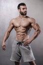 Brutal strong bodybuilder man posing in studio on grey backgroun