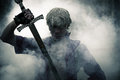 Brutal warrior with sword in smoke portrait of a Royalty Free Stock Images