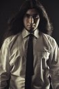 Brutal young guy portrait of handsome man with long hair over black background low key Stock Images