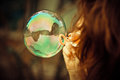 Bubble from bubble blower in girl hand blured italy forest in background Royalty Free Stock Photo