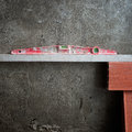 Bubble spirit level tool in red on costruction cement Stock Photos