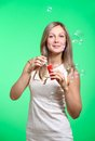 Bubbles cheerful girl inflates soap on a green background Stock Photography