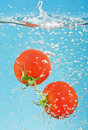 Bubbles forming in water after tomato are dropped Royalty Free Stock Photos