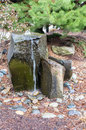 A bubbling water fountain in a garden Royalty Free Stock Photo
