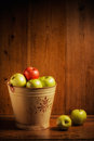 Bucket of apples green and red on wooden background Royalty Free Stock Images
