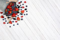 Bucket of berries spill a spilling onto a rustic white kitchen table high angle shot with the pail in the upper left corner Royalty Free Stock Images