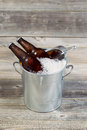 Bucket filled with ice and beer vertical view of two unopened bottles of sitting inside metal crushed iced rustic wood in Stock Photos