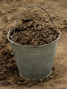 Bucket full of ground soil on dirt background Royalty Free Stock Photography