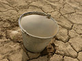 Bucket full of water on dry soil background Stock Photos