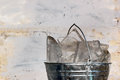 Bucket of ice on dirty wall background Royalty Free Stock Photo