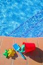 Bucket with plastic beach toys  near pool Royalty Free Stock Photo