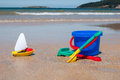 Bucket and spade colorful plastic toys a beach rake with boat on a beach Stock Image