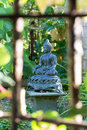 Buddha with bamboo view of a little in a garden inside a window Royalty Free Stock Images