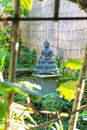 Buddha with bamboo view of a little in a garden inside a window Royalty Free Stock Photography