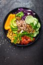 Buddha bowl dish with brown rice, avocado, pepper, tomato, cucumber, red cabbage, chickpea, fresh lettuce salad and walnuts. Healt Royalty Free Stock Photo