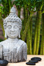 Buddha bust and hot stones huddha with bamboo in the background Royalty Free Stock Photos