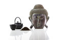Buddha head, teapot, cup and tea on a white background Royalty Free Stock Photo