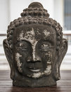 Buddha head in a wooden table Stock Photography