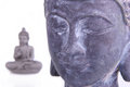 Buddha mood in the foreground of the picture you can see a s head made of stone while there is a meditating in the background Stock Photos