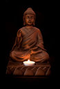 Buddha statue with a candle on a black background Royalty Free Stock Photo