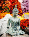 Buddha statue in fresh garden surrounded‎ by vibrant color flowers Stock Images
