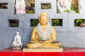 Buddha and taoism statues yellow painted statue small white statue on red table in outdoor garden Royalty Free Stock Photography