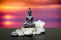 Buddha,zen stone,white orchid flowers.In the background sunrise over the sea Royalty Free Stock Photo
