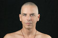 Buddhist looks to camera close up of a men looking shaved head and shirtless Royalty Free Stock Photo