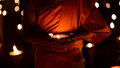 Buddhist monk hands holding candle cup in dark Royalty Free Stock Photo