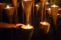 Buddhist monk hands lighting candle lighting candle in dark Royalty Free Stock Photo
