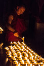 A buddhist monk lights butter lamps Royalty Free Stock Photo