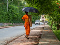 Buddhist monk in loas a walks downs a road luang prabang laos with an umbrella to shield him from the midday sun Stock Images