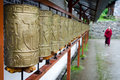 Buddhist monk and prayer wheels in a row Royalty Free Stock Photo