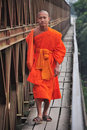 Buddhist monk walking on the bridge Stock Photo