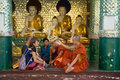 Buddhist monks communicate with the European tourists in one of the temples of the Shwedagon pagoda. Yangon, Myanmar
