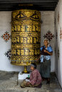 Buddhist pilgrim praying with a prayer wheel in Chimi Lhakang Monastery Royalty Free Stock Photo