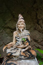 Buddhist statue with a third eye in a rock in the ancient forest Stock Photo