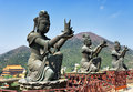 Buddhist statues praising and making offerings to the tian tan buddha the po lin monastery and the lantau peak in the background Royalty Free Stock Image