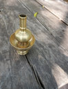 Buddist water vase made from brass on the rustic timber table with nature background Royalty Free Stock Photos