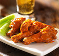Buffalo chicken wings with beer close up photo of celery and in the background Stock Image