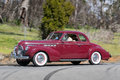 1940 Buick Special Coupe driving on country road Royalty Free Stock Photo