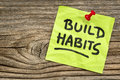 Build habits reminder self development concept handwriting on a green sticky note against grained and knotted wood board Royalty Free Stock Photo