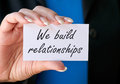 We build relationships text written on a small white card closeup held in a woman s hand black and blue background Stock Photo