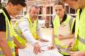 Builder On Building Site Discussing Work With Apprentice Royalty Free Stock Photo