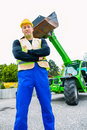 Builder in front of construction machinery or driver standing on building site Stock Photos